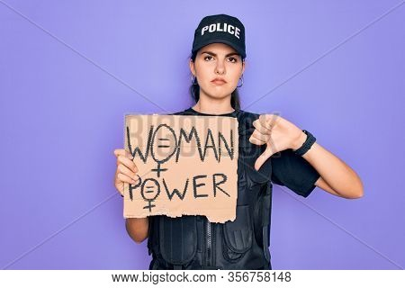 Police woman wearing security bulletproof vest uniform holding woman power protest cardboard with angry face, negative sign showing dislike with thumbs down, rejection concept