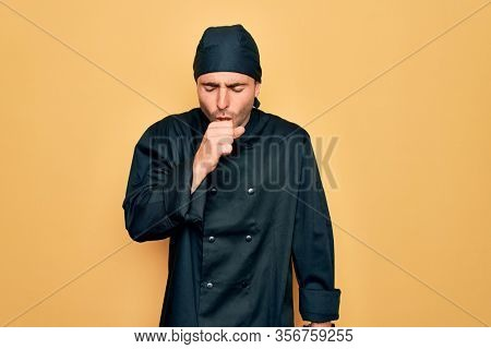 Young handsome cooker man with blue eyes wearing uniform and hat over yellow background feeling unwell and coughing as symptom for cold or bronchitis. Health care concept.
