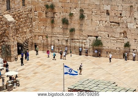 JERUSALEM, ISRAEL - JULY 04, 2016: View from above of plaza and people praying at Western Wall  - holy place in judaism, stone ancient remains of Second Temple in Old City of Jerusalem, Israel.