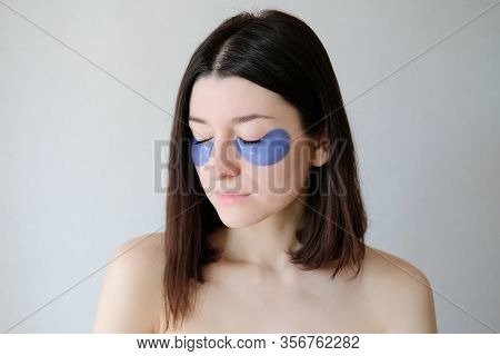 Beautiful Woman With Closed Eyes Applying Under Eye Patches For Puffy. Face Skin Care And Beauty Tre
