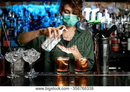 Woman Bartender In Medical Mask Treats Her Hands With Disinfector