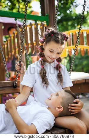 Cute Child Boy Lying On His Pretty Sister Legs Sitting On The Bench At The Playground. Concept Of Su