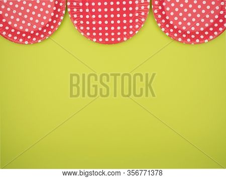 Colored Paper Plates On A Bright Green Background. Disposable Ware.the View From The Top.