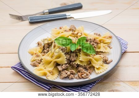 Ready-to-eat Pasta Navy With Minced Meat And Basil Leaves On A Plate And Cutlery On A Wooden Table.