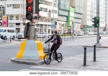 Abu Dhabi, Uae - March 10, 2020: Girl In The City On A Bike On Traffic Signal Wearing Face Mask, Pre
