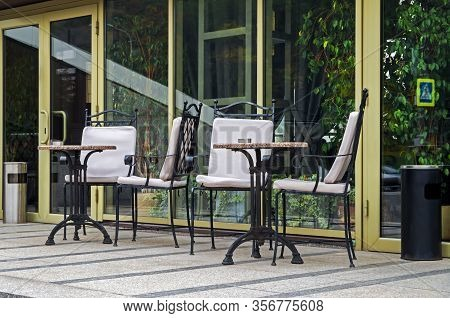 Tables And Chairs On Summer Terrace Of Winter Garden Of Apartment Building