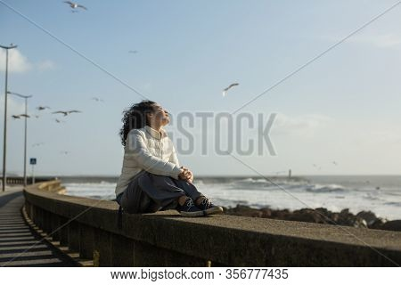 Beautiful multicultural asian woman sits on the waterfront during the surf and gulls around. Mixed-race tourist female in spring outdoor.