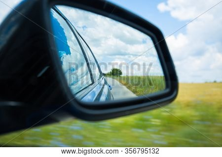 Side Rear-view Mirror Car Reflection Of A Winding Road In A Forest Or Countryside. Dramatic Scenery