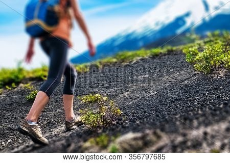 Young woman hiker walks on the loose rocky trail with slope of the volcano on the background