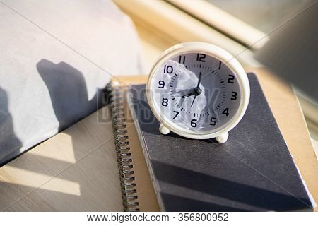 Close U White Alarm Clock 8 Oclock Am, On Wooden Table Near Bed With Warm Morning Light From Window,