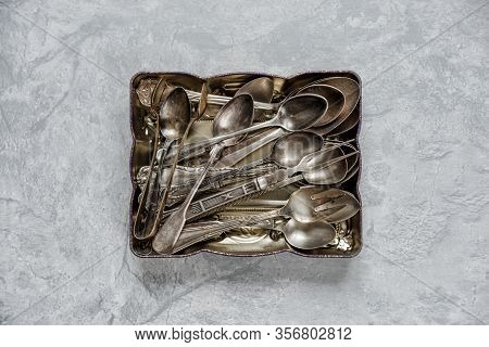 Various Silver Flatware In A Metal Tray On The Background Of Gray Stone Tabletop