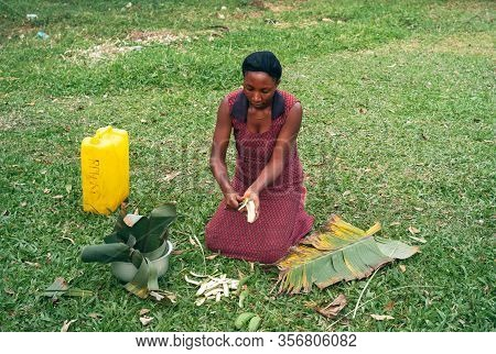 Kabale, Uganda - July 24 2011: Woman Kneeling And Preparing Cooking Banana. Black Local, Female Cook