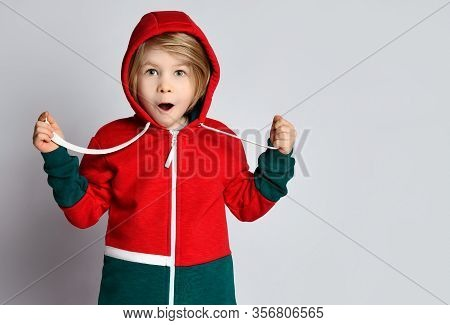 Portrait Of Frolic Excited Surprised Blond Kid Boy In Dark Gray And Red Hoodie With His Cowl Over Hi