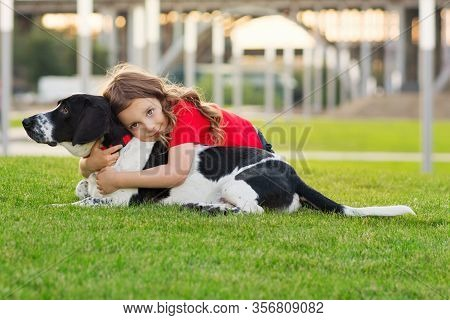 Beautiful Young Girl Is Hugging Her Pet. Cute Photo Of Dog And Its Owner Relaxing On The Grass. Fait