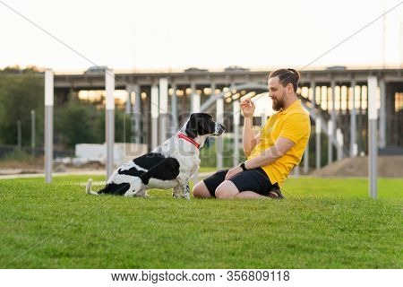 Handsome Hipster Man On A Walk With A Dog. Сlose Friendship Loving Bond Between Owner And Pet Huntin