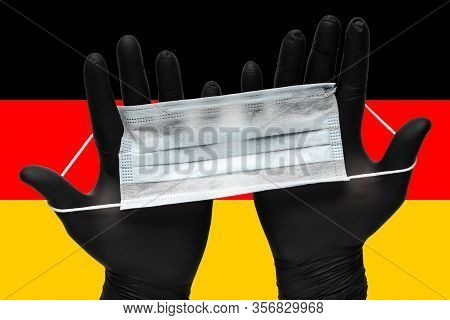 Doctor Holds Face Mask In Hands In Black Medical Gloves On Background Colors Flag Of Germany Or Germ