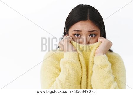 Close-up Portrait Of Timid Gloomy Cute Asian Girl, Frowning Pulling Sweater On Face And Looking Came