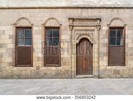Facade Of Old Abandoned Stone Decorated Bricks Wall With Arched Wooden Door And Three Wooden Shutter