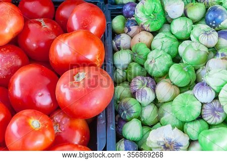 Tomatillo And Red Tomatoes On Black Plastic Food Crate At Farmer Market In Washington, America