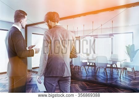Two Businessmen Talking Near Modern Conference Room With White And Glass Walls, Dark Wooden Floor An