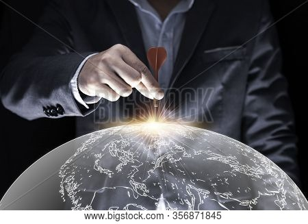 Businessman Hand Holding And Trowing Red Dart To Target Board On Black Background And World Map .bus