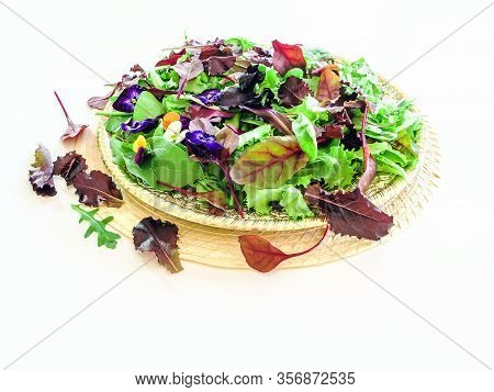 Mix Salad On A Salver, Top View. Green Salad Leaves Mix On White Table. Plate, Herbs. Fresh Mixed Ve