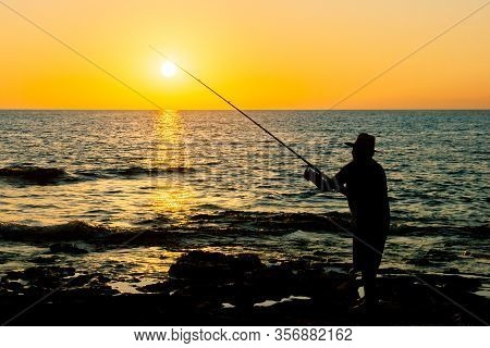 Fisherman At Sunset Throws Tackle Into The Sea. Silhouette Of A Fisherman Fishing At Sunset.