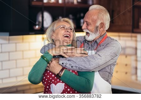 Beautiful Senior Couple Is Dancing And Smiling While Cooking Together In Kitchen. Quarantine. Health
