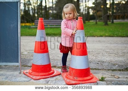 Adorable Toddler Girl Playing With Safety Traffic Cones While Walking In Park