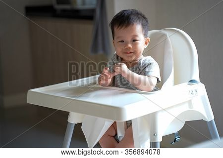 Close Up Asian Little Baby Sitting In Highchair, Making A Mess After Finished Eating Her Breakfas In