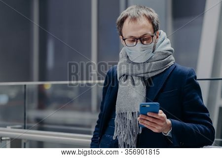 Photo Of Man Watches News On His Phone, Wears Protective Mask, Protects From Air Contamination Or Co