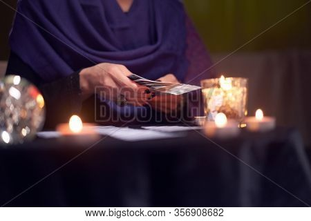 Close-up of fortune teller female divining on cards sitting at table with burning candles, magic ball