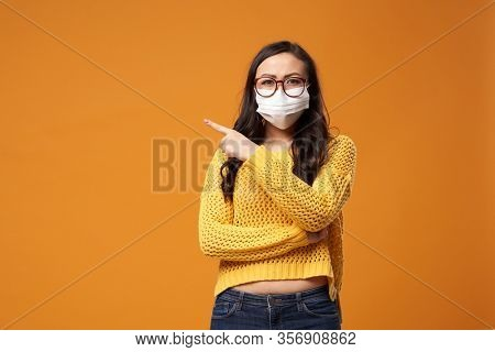 Chine woman with glasses and medical mask pointing hand to side in studio