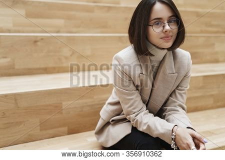 Business, Career And Women Concept. Portrait Of Cheerful Successful Young Woman In Beige Jacket, Sit