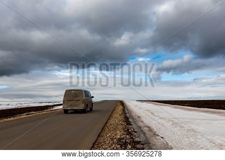 A Dirty Car Is Driving Along A Narrow Deserted Highway. The R Oad G Oes O Ver The H Orizon, A Nd T H