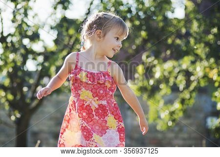 Cute Little Two Years Old Girl In Red Floral Dress Is Outdoors.