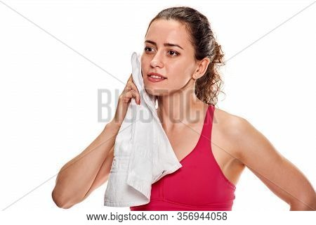 Portrait Of Tired Young Sportswoman Wiping Sweat After Training