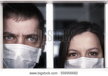 Quarantine. A Sick Man And Woman In Protective Medical Masks Look Through The Hospital Bars. Emotion