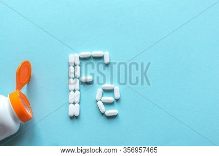 Iron Supplement Pills, Anemia Treat. Green Pills Forming Shape To Fe Alphabet On Blue Background, To