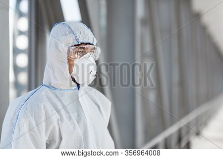 Man Wearing Protective Biological Suit And Mask Due To Coronavirus Global Pandemic Warning And Dange