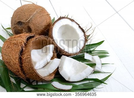 Coconut. Whole Coconut, Shell And Green Leaves On A White Wooden Background. Big Nut. Tropical Fruit