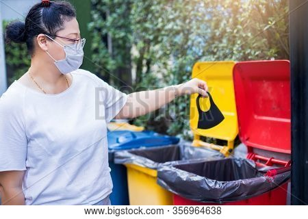Asian Women Throwing Face Masks Into Trash. The Used Mask Is Cut To Prevent Reuse In The Bucket. Med