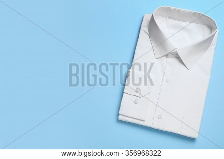 Stylish White Shirt On Light Blue Background, Top View With Space For Text. Dry-cleaning Service