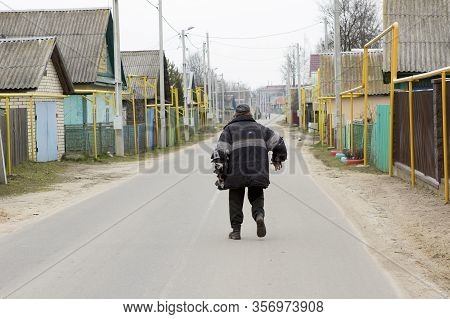 A Lonely Drunk Asocial Dirty Ragged Untidy Man Zombie Walks Along A Village Street. Drunkenness In T