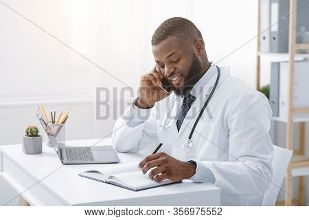 Young African Doctor Talking To Patient On Phone While Working In Modern Clinic, High Quality Servic