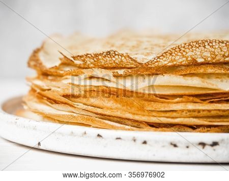 Stack Russian Homemade Thin Pancakes On White Plate On Wood Background. Traditional Wheat Pancakes F
