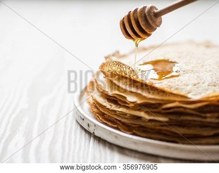 Stack Russian Homemade Thin Pancakes On White Plate And Honey Flows From A Wooden Spoon. Traditional