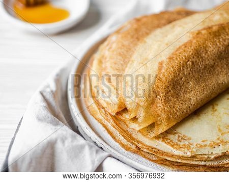 Stack Russian Homemade Thin Pancakes On A White Plate And Wood Honey Spoon And Honey On Small White