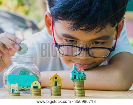 Asian Boy Holding Coins Drop A Container Saving Money To Save Money Invest For Future And Buy Home.c