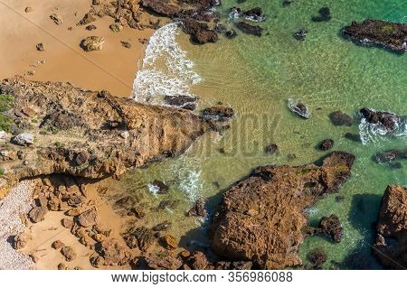 Beautiful Seaside Background With Cliffs And Pristine Beach With Clear Water And Yellow Sand. Seasid